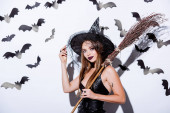 Photo girl in black witch Halloween costume with broom near white wall with decorative bats