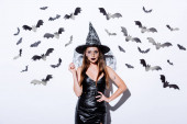 Photo girl in black witch Halloween costume near white wall with decorative bats
