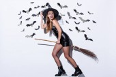 Photo happy girl in black witch Halloween costume on broom near white wall with decorative bats