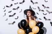 dívka v černé čarodějnice Halloween kostým drží balónky v blízkosti bílé zdi s dekorativními netopýry