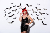 girl in devil Halloween costume near white wall with decorative bats