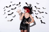 Photo girl in black witch Halloween costume with red hair holding skull near white wall with decorative bats