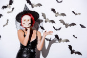 Photo girl in black witch Halloween costume with red hair holding skull in front of face near white wall with decorative bats