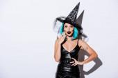 šokované dívka v černošky halloween kostým s modrými vlasy na bílém pozadí