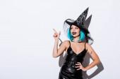 Lächelndes Mädchen im schwarzen Hexenhalloween-Kostüm mit blauen Haaren, die mit dem Finger auf weißem Hintergrund zeigen