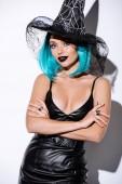 Fotografie Mädchen in schwarzem Hexenhalloween-Kostüm mit blauen Haaren und verschränkten Armen auf weißem Hintergrund