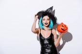 sexy girl in black hexe halloween kostüm mit blauen haaren hält gruselig geschnitzten kürbis auf weißem hintergrund