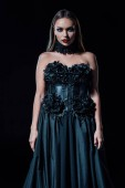 scary vampire girl in black gothic dress isolated on black