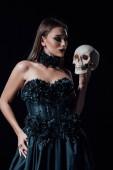 scary vampire girl in black gothic dress holding human skull isolated on black