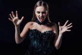 scary vampire girl with fangs in black gothic dress isolated on black