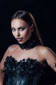 scary vampire girl with fangs in black gothic dress looking at camera isolated on black