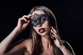 naked scary vampire girl in masquerade mask touching face isolated on black