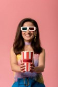 happy young stylish disco girl in 3d glasses holding striped paper bucket with popcorn isolated on pink