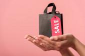 oříznutý pohled na dívku držící nákupní tašku s nápisem na etiketě izolované na růžové