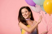 Photo young smiling party girl holding festive balloons isolated on pink