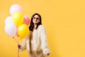 mosolygós party lány hamis szőrme kabát és napszemüveg tartja léggömbök izolált sárga