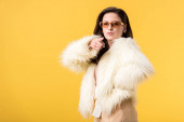 girl in faux fur jacket and sunglasses pointing with finger at camera isolated on yellow