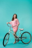 excited girl in pink outfit with retro bike on turquoise background