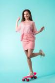 glückliches Mädchen im rosa Outfit posiert auf Penny Board auf türkisfarbenem Hintergrund