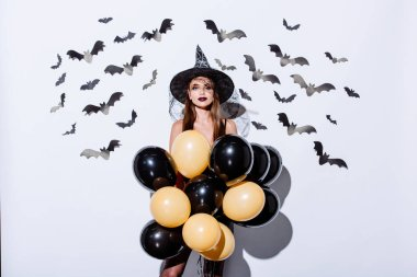 girl in black witch Halloween costume holding balloons near white wall with decorative bats