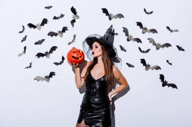 Girl in black witch Halloween costume holding carved spooky pumpkin near white wall with decorative bats stock vector
