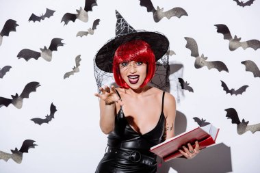 Girl in black witch Halloween costume with red hair holding book near white wall with decorative bats stock vector