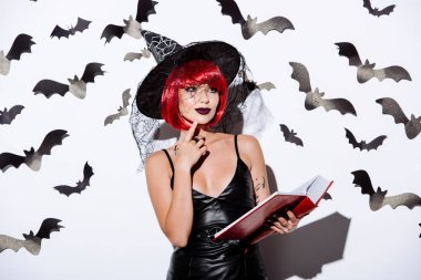 Thoughtful girl in black witch Halloween costume with red hair holding book near white wall with decorative bats stock vector