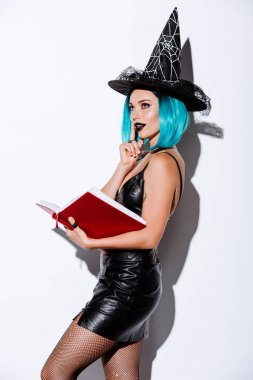 Sexy girl in black witch Halloween costume with blue hair holding book on white background stock vector