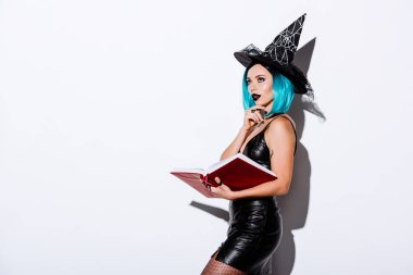 Pensive sexy girl in black witch Halloween costume with blue hair holding book on white background stock vector