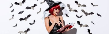 Panoramic shot of girl in black witch Halloween costume with red hair reading book near white wall with decorative bats stock vector