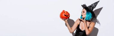 Panoramic shot of sexy girl in black witch Halloween costume with blue hair blowing kiss to spooky carved pumpkin on white background stock vector