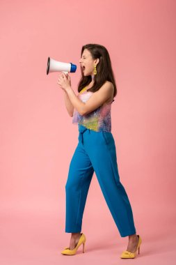 full length view of angry young stylish disco girl screaming in megaphone on pink