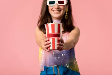 Selective focus of happy young stylish disco girl in 3d glasses presenting striped paper bucket with popcorn isolated on pink stock vector
