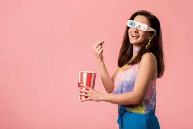 Side view of happy young stylish disco girl in 3d glasses eating popcorn isolated on pink stock vector