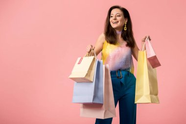 happy stylish disco girl holding shopping bags isolated on pink