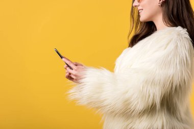 Cropped view of happy party girl in faux fur jacket and sunglasses holding smartphone isolated on yellow stock vector