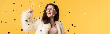 panoramic shot of excited party girl in faux fur jacket and sunglasses standing under confetti with champagne isolated on yellow