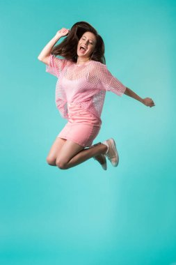 excited girl with open mouth in pink outfit jumping isolated on turquoise