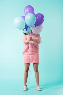girl in pink outfit holding balloons in front of face on turquoise background