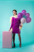 boldog party lány lila ruhában tollakkal tartja lufik közelében hatalmas ajándék doboz türkiz