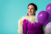 happy party girl in purple dress with feathers holding balloons isolated on turquoise