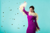 happy party girl in purple dress with feathers dancing under falling confetti isolated on turquoise