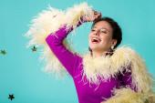Fényképek boldog party lány lila ruhában tollakkal alá esik konfetti elszigetelt türkiz