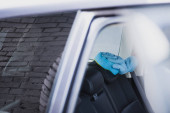 partial view of car cleaner in rubber glove cleaning car set with sponge