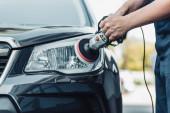 ořezaný pohled na čistič aut leštící světlomet s leštícím strojem