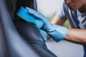 částečný pohled na čistič aut otírající autosedačku s houbičkou