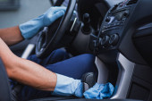 cropped view of car cleaner in rubber gloves sitting on drivers seat in car