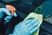 částečný pohled na čistič aut v gumových rukavicích čistící vůz s hadrem