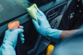 oříznutý pohled na čistič aut drží hadr a sprej láhev při čištění dveří auta