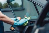 Fotografie oříznutý pohled na čistič aut otírající dveře s hadrem